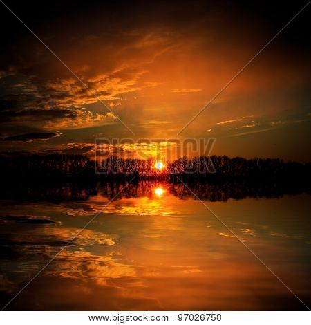 Red sunset over lake water surface
