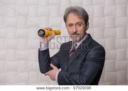 Mature businessman with flashlight