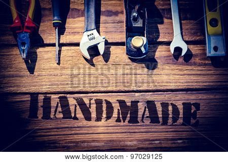 The word handmade against desk with tools