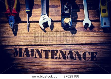 The word maintenance against desk with tools