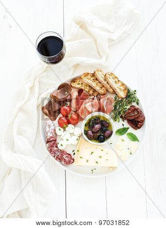 Wine appetizer set. Cherry-tomatoes, parmesan cheese, meat variety, bread slices, dried tomatoes, ol