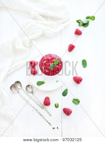 Raspberry sorbet ice-cream with mint leaves  and spoons on white background