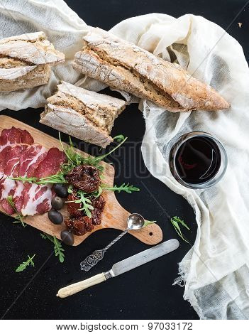Wine appetizer set: vintage dinnerware, french baguette broken into pieces, dried tomatoes, olives,