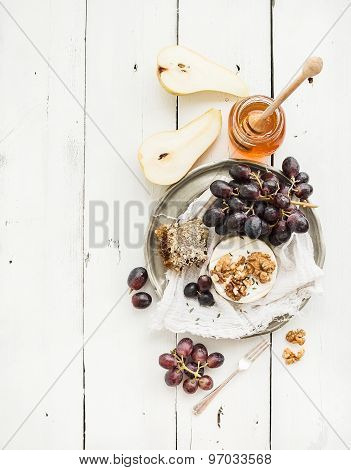 Camembert cheese with grape, walnuts, pear and honey on vintage metal plate over white rustic wood
