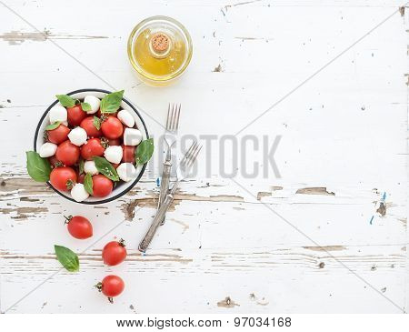 Caprese salad: cherry-tomatoes and mozzarella in metal bowl with olive oil on rustic white wooden ba
