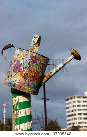 An Old Watering Can Painted With Colorful Floral Decorations