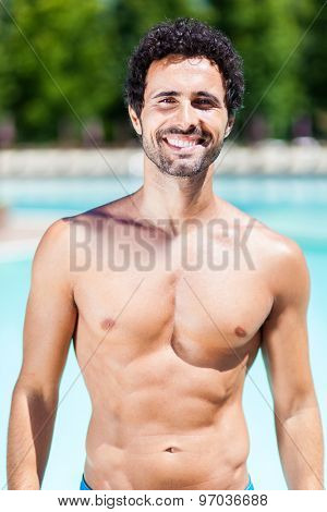 Handsome man sun bathing at a swimming pool