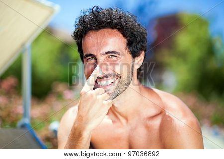 Man applying sun screen on his nose
