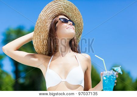 Woman in hat relaxing at the pool with cocktail