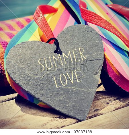 the text summer love written in a heart-shaped slate stone and a pair of rainbow flip-flops on a boardwalk, slight vignette added