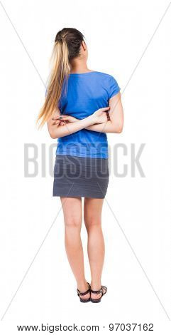 back view standing young beautiful  woman. girl  watching. Rear view people collection. Isolated over white background. Girl in a gray skirt and blue shirt stands with his arms crossed behind his back