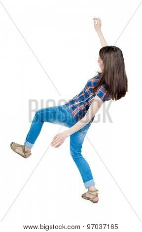 Back view woman Balances waving his arms.   Standing young girl in jeans. Rear view people collection.   A young girl in a checkered blue with red stripes and slipped trying not to fall.