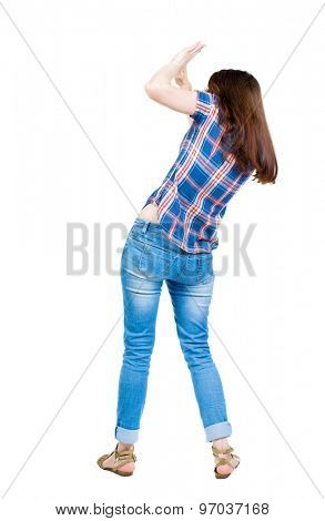 back view woman protects hands from what is falling from above. A young girl in checkered blue with red stripes frightened covers his face to protect themselves from what is above