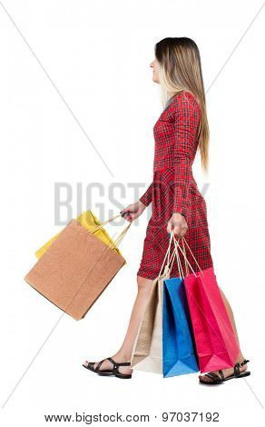 back view of going  woman  with shopping bags . beautiful girl in motion.  backside view of person.  Isolated over white background. Long-haired girl in a red plaid dress is swinging shopping bags.