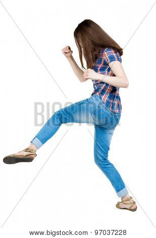 skinny woman funny fights waving his arms and legs. Isolated over white background. A young girl in a checkered blue with red stripes make kick-boxing punch.