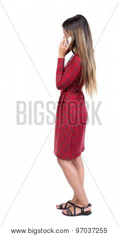 back view of standing young beautiful  woman and using a mobile phone. girl  watching. Rear view people collection.  backside view person. Long-haired girl in a red plaid dress talking on the phone.