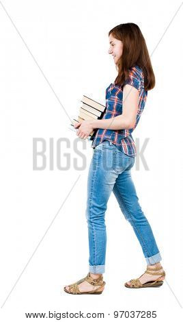 girl carries heavy pile of books. side view. Rear view people collection. backside view person. young girl in checkered blue with red stripes goes from right to left smiling and carries stack of books