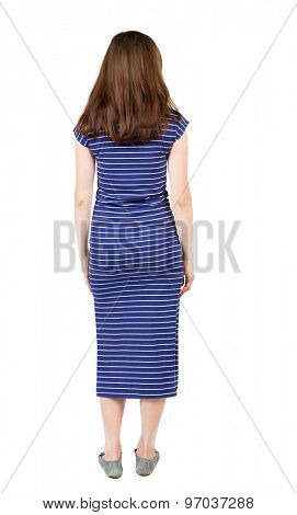 back view of standing young beautiful  woman.  girl  watching. Rear view people collection.  Isolated over white background. Girl in a blue striped dress standing with her hands and looking ahead.