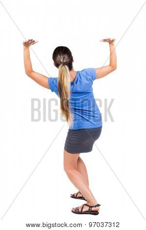 back view of woman  protects hands from what is falling from above. .  Isolated over white background. Girl in a gray skirt and blue shirt sitting down holding something heavy overhead.