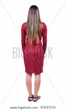 back view standing young beautiful woman. girl watching. Rear view people collection.   Isolated over white background. Long-haired girl in red plaid dress standing and looking in front of him
