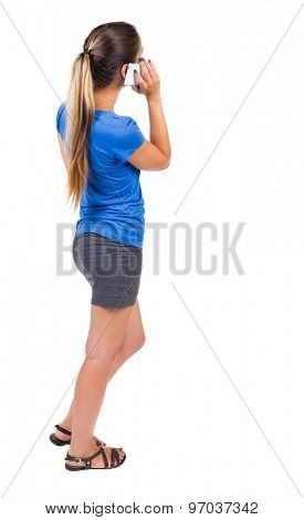 back view of standing young beautiful  woman and using a mobile phone. girl  watching.   Isolated over white background. Girl in a gray skirt and blue shirt talking on a white phone.phone.