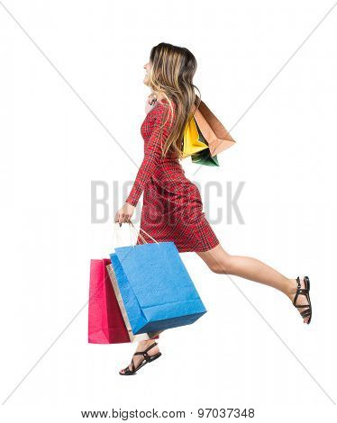 side view of a woman jumping with shopping bags. beautiful brunette girl in motion.  backside view person.  Isolated over white background. Long-haired girl in a red plaid dress runs with paper bags