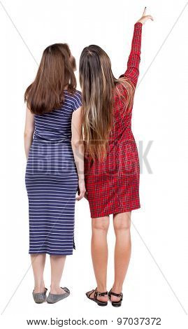 Back view two pointing young girl. Rear view people collection. backside view person. beautiful woman friends showing gesture. Rear view. Isolated over white background. Two girls in dresses show mark