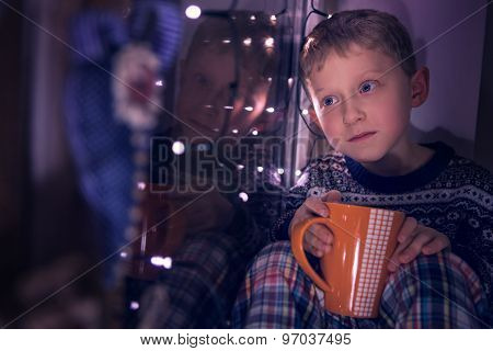 Boy Sitting On Window Decorated For Christmas Eve
