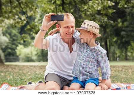 Father And Son Take A Self Picture With A Phone