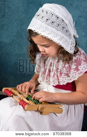 Sweet victorian girl posing in the old style with an abacus