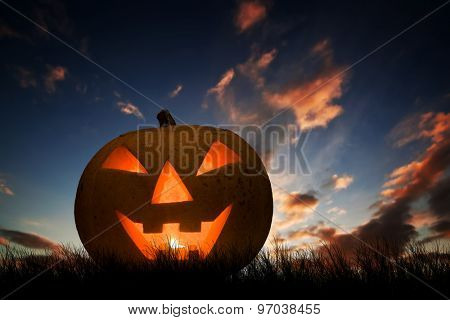 Halloween pumpkin glowing under dark sunset, night sky. Hand carved jack o'lantern with scary face