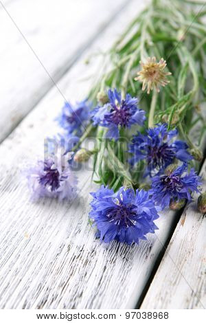 Blue wildflowers on wooden table, closeup
