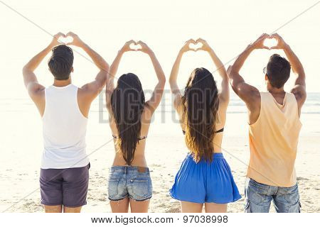 Group of friends together at the beach and making hearth shapes with her hands