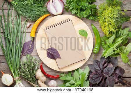 Fresh garden herbs and notepad for your recipes on wooden table