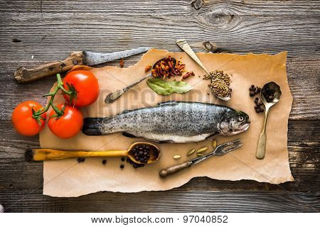 fresh raw trout with tomatoes and spices on a wooden background