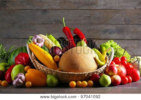Heap of fresh fruits and vegetables on wooden background