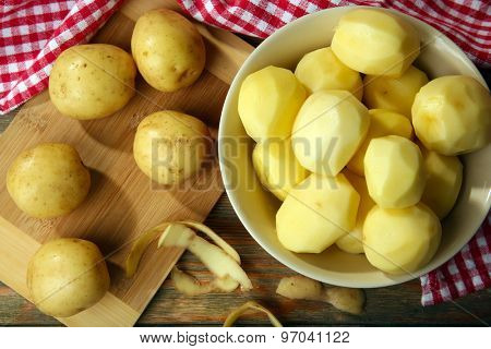 Peeled new potatoes in bowl on wooden table with napkin, top view