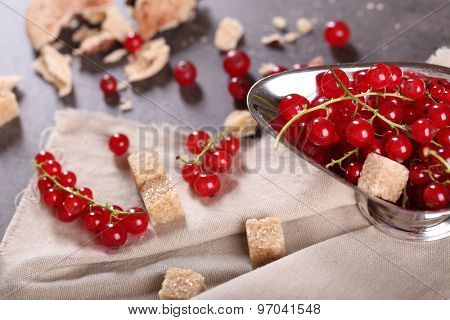 Ripe red currants with lamp sugar on table with sackcloth, closeup