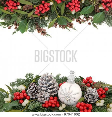 Christmas background border with snowflake bauble, holly, mistletoe, fir, snow covered pine cones and traditional greenery over white.