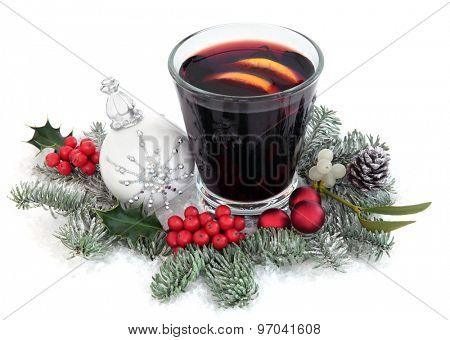 Christmas mulled wine on snow with bauble decoration, holly, mistletoe and winter greenery on snow over white background.