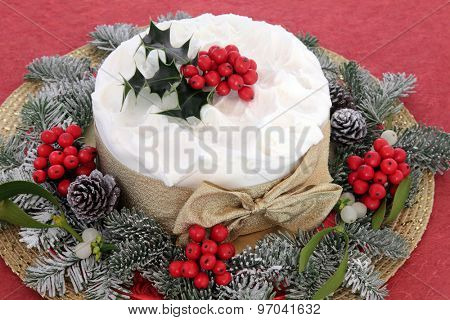 Christmas cake with holly, mistletoe and winter greenery over red background.