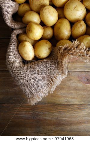 New potatoes on sackcloth on wooden table, top view