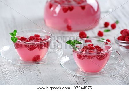 Cups and teapot of raspberry drink with berries on wooden table close up