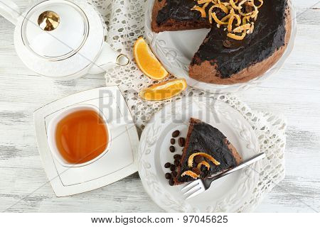 Cake with Chocolate Glaze and orange on plate, on wooden background
