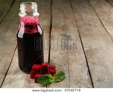 Glass bottle of beet juice on wooden table, closeup