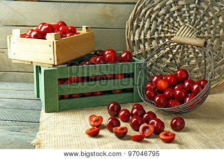 Sweet cherries with green leaves  in basket and wooden boxes, on wooden background