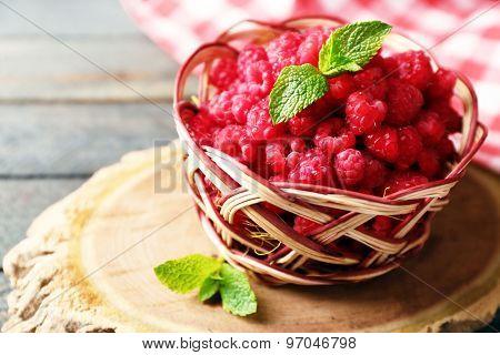 Sweet raspberries in wicker basket on wooden  background