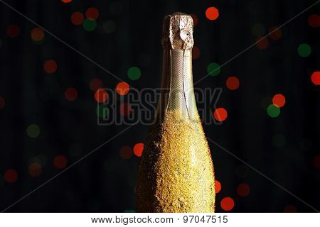 Decorative champagne bottle on dark colorful spotted background