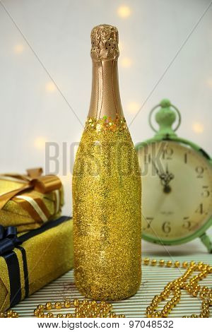 Decorative champagne bottles with present boxes, beads and clock on light background