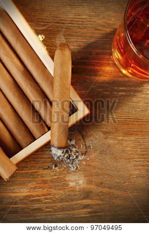 Cigars and burning one with cognac on wooden table, top view